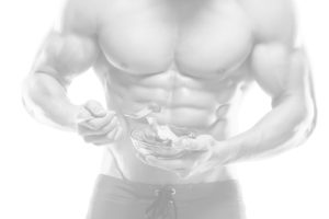Muscular guy eating healthy whole food for sports performance nutrition