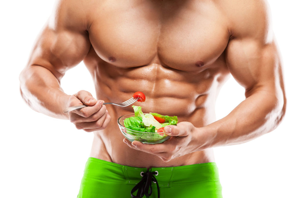 Muscular guy eating healthy green salad