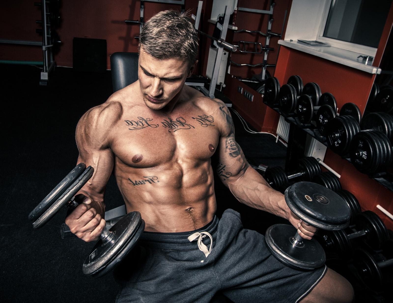 Muscular guy holding dumbells