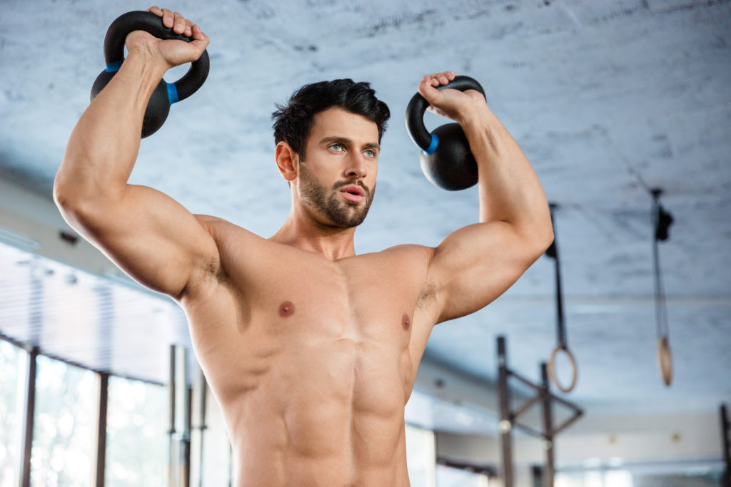 Muscular man shoulder pressing kettle bells