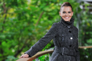 Happy smiling woman posing outdoors in a business casual coat