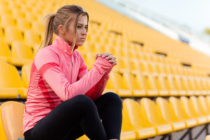 Portrait of a young woman in sports wear sitting on the chair at outdoor stadium