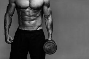 Muscular guy holding a dumbbell