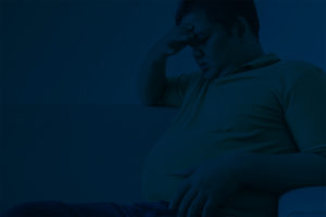 Dark background with overweight man sitting depressed on a couch looking at his belly